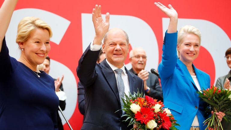 Social Democratic Party (SPD) leader and top candidate for chancellor Olaf Scholz, Mecklenburg-Western Pomerania state Prime Minister Manuela Schwesig and SPD member Franziska Giffey wave as they carry bouquets of flowers at their party leadership meeting, one day after the German general elections, in Berlin, Germany