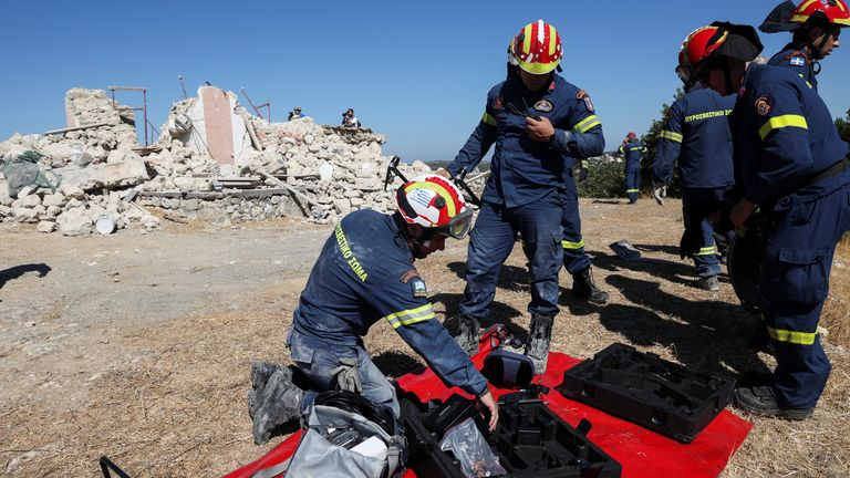 Firefighters check their equipment next to the ruins of a destroyed church after an earthquake in Arkalukouri, Crete, Greece