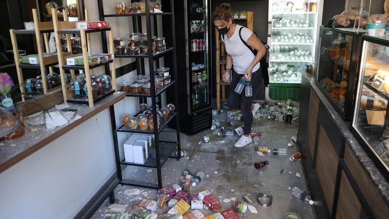 A woman moves among goods that fell on the floor following an earthquake, at a shop in the town of Arkalochori on the island of Crete, Greece