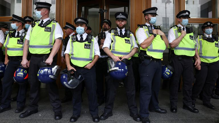 Police officers stand guard as members of the Official Voice group protest at Canary Wharf in London, Britain, September 3, 2021. REUTERS/Tom Nicholson