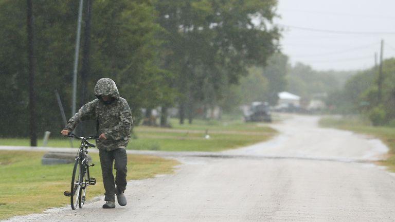 A pedestrian walks his bike in the rain as Tropical Storm Nicholas approaches in Matagorda, Texas on Monday, Sept. 13 pic:AP