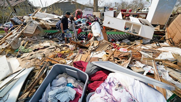 Jose Duran, left, helps his mother, Cruz Palma sift through what remains of her home in the aftermath of Hurricane Ida, Thursday, Sept. 2, 2021, in Golden Meadow, La. (AP Photo/David J. Phillip) PIC:AP
