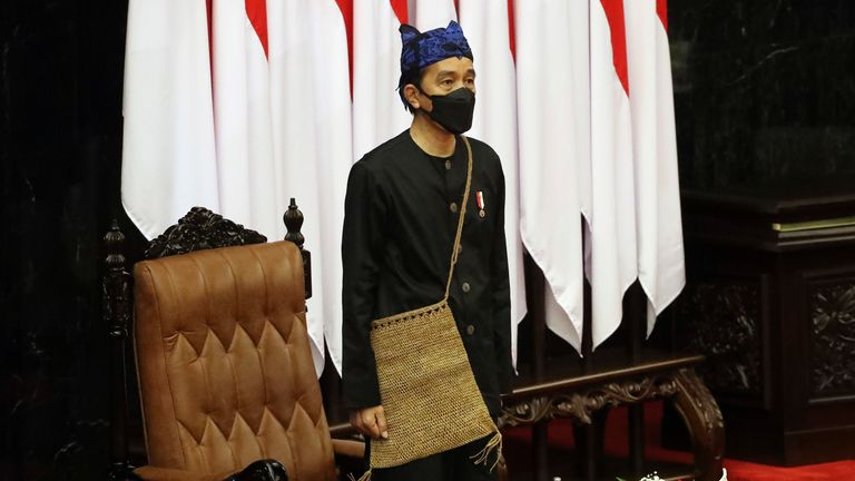Indonesian President Joko Widodo listens to the national anthem after delivering his annual State of the Nation Address ahead of the country...s Independence Day, at the parliament building in Jakarta, Indonesia, Monday, Aug. 16, 2021. (Bagus Indahono, Pool photo via AP)