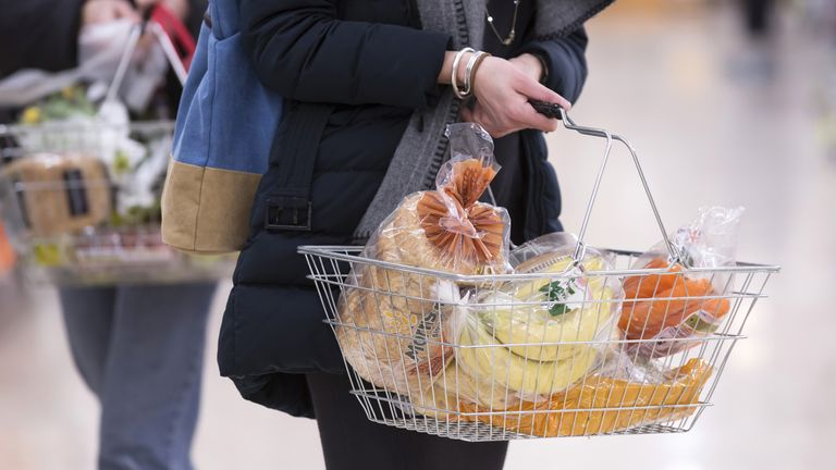 Undated file photo of a woman shopping holding a basket. Issued 1/9/2021
