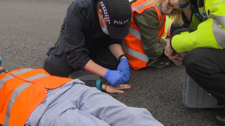 Insulate Britain protesters glue themselves to the road.