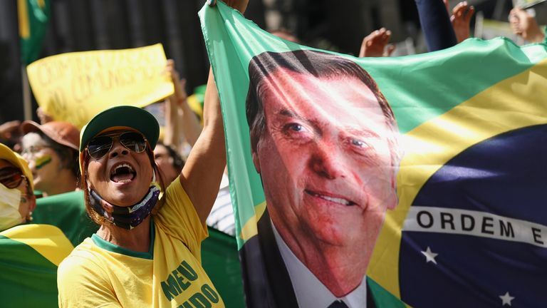 A supporter of Mr Bolsonaro holds a banner with his image during a march in a show of support for his attacks on the country's Supreme Court