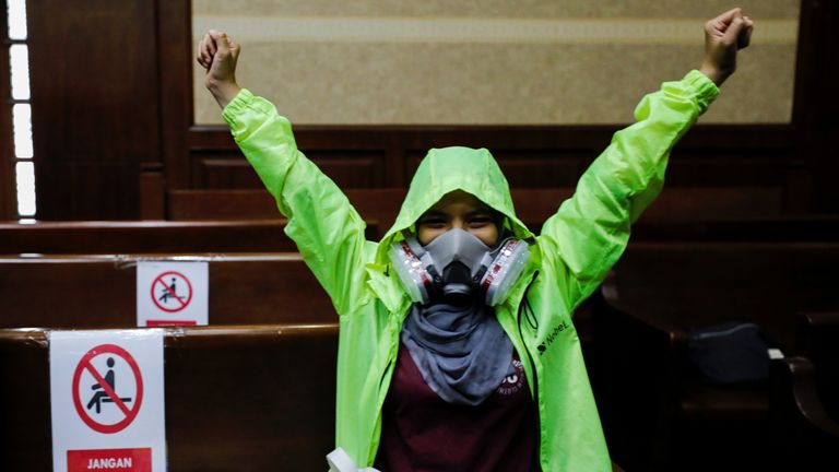 An environmental activist wearing a protective mask reacts inside the courtroom during the hearing