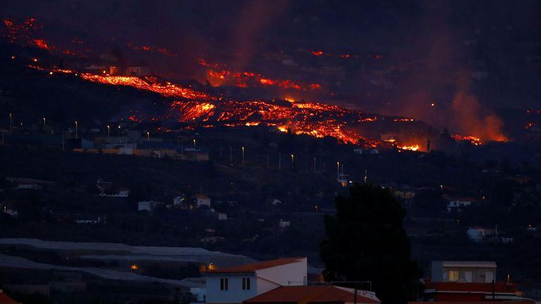 La lave coule derrière les maisons après l'éruption d'un volcan en Espagne