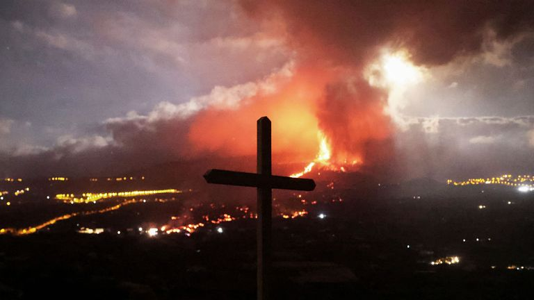 A cross is seen as lava and smoke rise following the eruption of a volcano on the Island of La Palma, in Los Llanos de Aridane, Spain September 21, 2021. Picture taken September 21, 2021. REUTERS/Nacho Doce