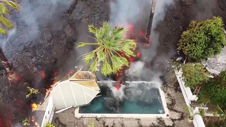 Drone view of lava swallowing swimming pool and homes on La Palma