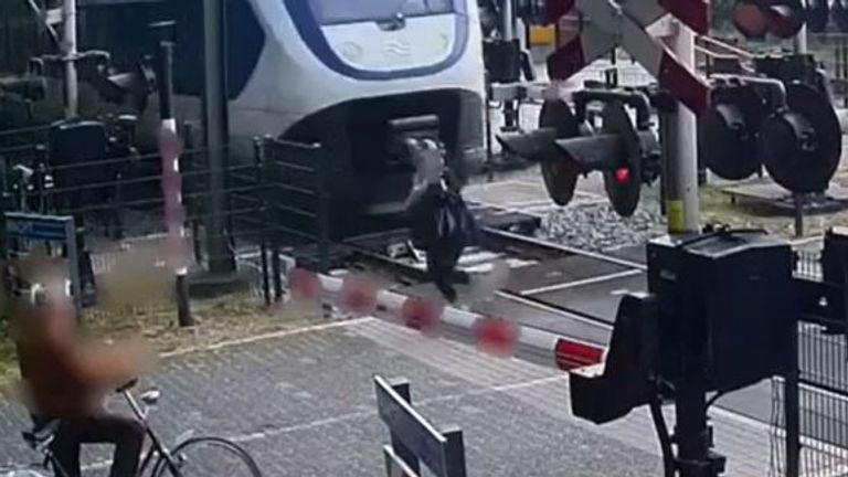 Woman has lucky escape after walking over level crossing with barriers down