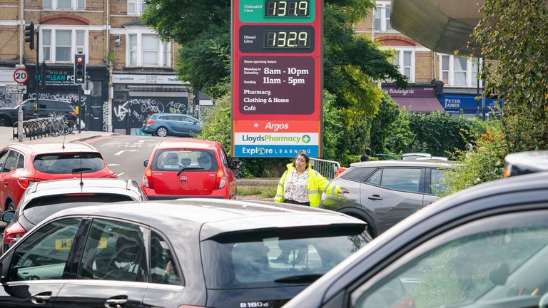 A member of staff directs drivers in a queue for fuel at a closed Sainsbury's petrol station in south London. Picture date: Sunday September 26, 2021.