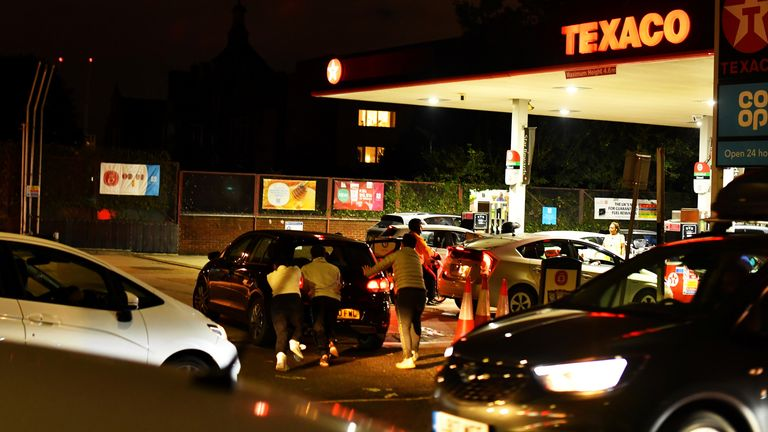 People push as a car, which has run out of petrol, the final few meters at a Texaco fuel station in south London