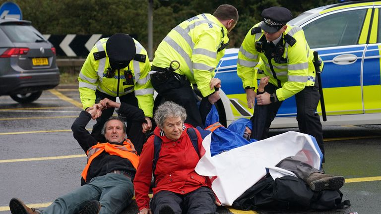 Police officers detain protesters from Insulate Britain occupying a roundabout leading from the M25 motorway to Heathrow Airport in London. Picture date: Monday September 27, 2021.