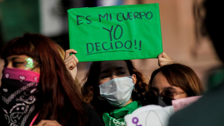 """A woman holds up a banner which reads """"My body, I decide"""" during a protest to celebrate the decision"""