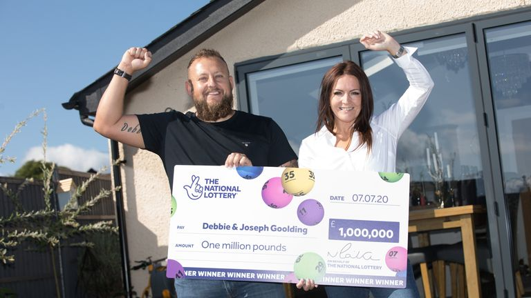 Ms Goolding, who won £1m, holds up the cheque with her husband Joseph