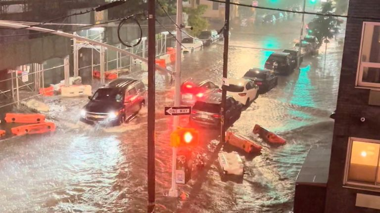 A vehicle moves along a flooded road in Williamsburg, in the Brooklyn borough of New York City
