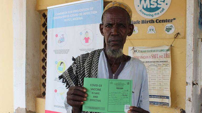 A Nigerian man who has been jabbed displays his COVID-19 vaccination certificate. Pic: AP