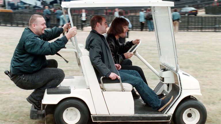 Liam Gallagher of Oasis drives around Knebworth Park in Hertfordshire in a golf buggy