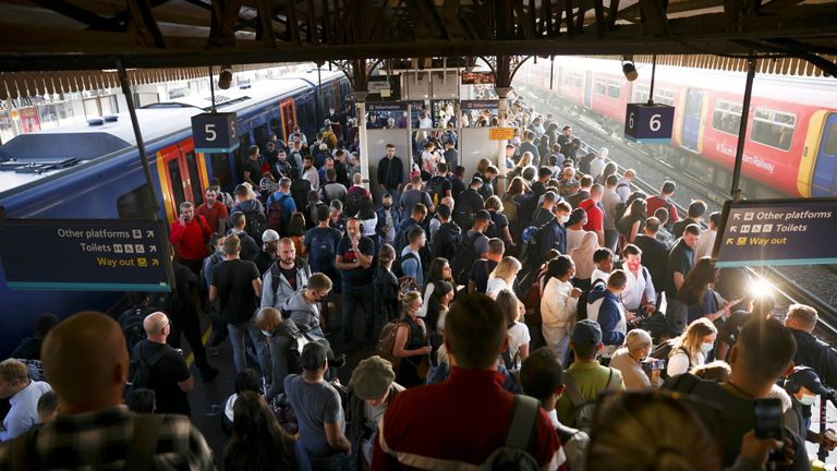 Commuters stand on a platform at Clapham Junction station during morning rush hour in London, Britain, September 8, 2021