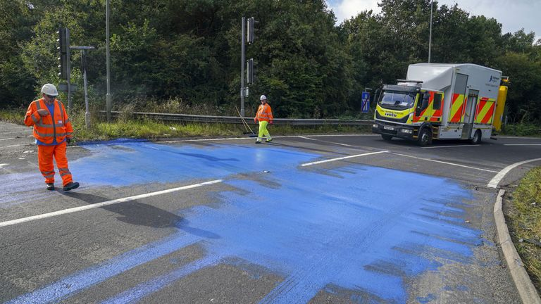 Highways England workers on the exit slip road of the M25 motorway near Leatherhead after protestors blocked the road and left paint on it. Picture date: Friday September 17, 2021.