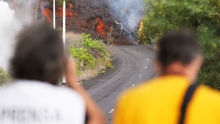Two people watch on as lava advance through the area of Cabeza de Vaca