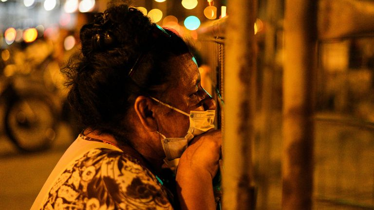 A woman waits outside of the prison waiting for news