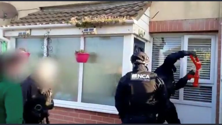 One officer was seen battering down the door as the NCA carried out the dawn raid