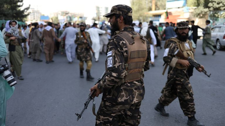 Taliban soldiers stand in front of protesters during the anti-Pakistan protest in Kabul, Afghanistan