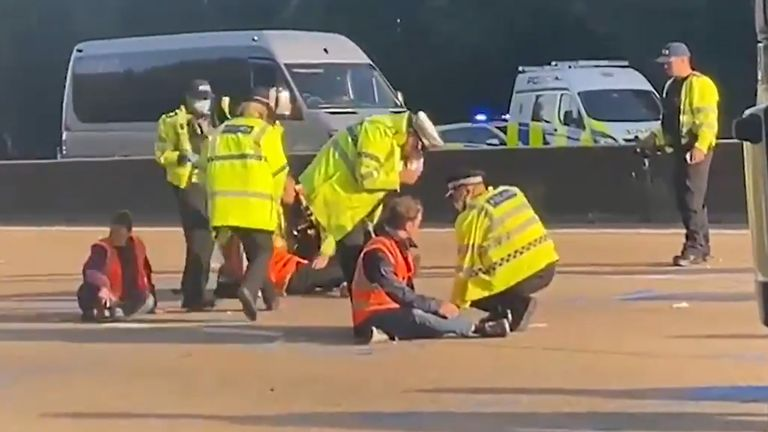 mage courtesy of LBC showing police officers removing Insulate Britain activists from the M25 between junctions 9 and10 where the climate protesters carried out a further action after demonstrations which took place last week across junctions in Kent, Essex, Hertfordshire and Surrey. Picture date: Tuesday September 21, 2021.
