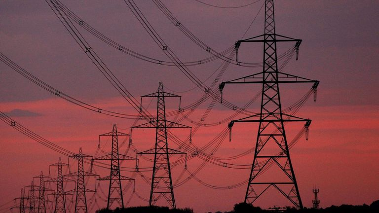 FILE PHOTO: The sun rises behind electricity pylons near Chester, northern England October 24, 2011. REUTERS/Phil Noble/File Photo