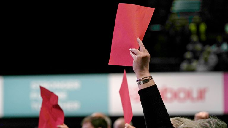 Delegates hold up a red cards as a group of hecklers attempt to interrupt the keynote speech of leader of the British Labour Party Keir Starmer at the annual party conference in Brighton, England, Wednesday, Sept. 29, 2021. (AP Photo/Alastair Grant)
