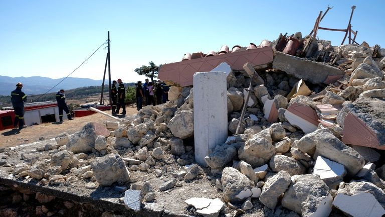Firefighters stand next to a demolished Greek Orthodox church of Profitis Ilias after a strong earthquake in Arkalochori village on the southern island of Crete, Greece PIC:AP