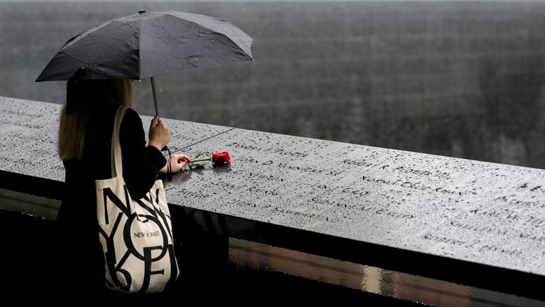 A person stands in the rain with a red rose at the 9/11 Memorial