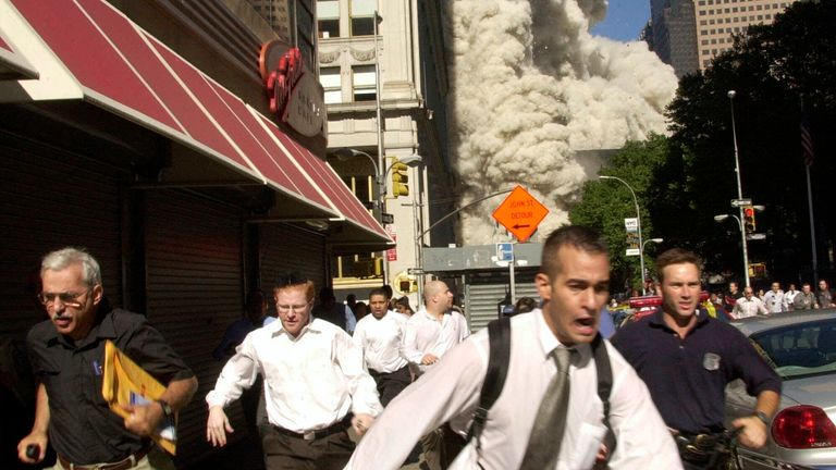 People flee after the collapse of one of the towers. Pic: AP