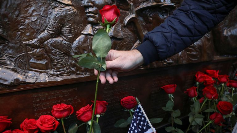 A family member of 9/11 victims adds a flower at FDNY Ten House
