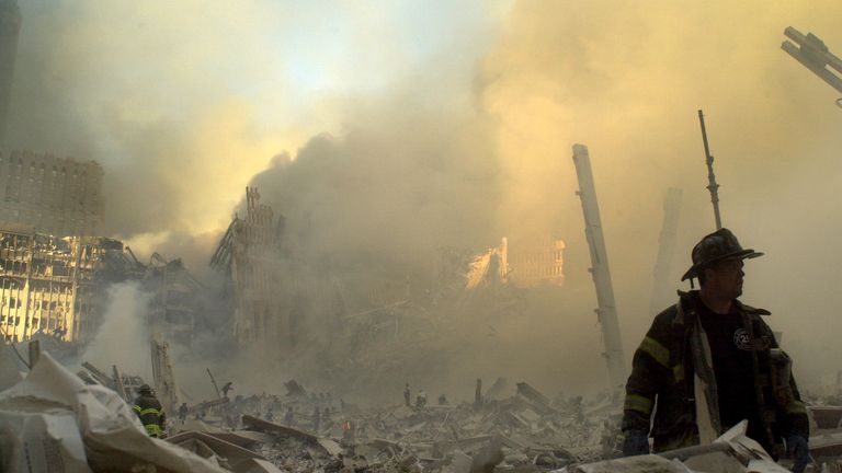 A lone firefighter moves through piles of debris at the site of the World Trade Center in New York, Tuesday, Sept. 11, 2001. Two Planes crashed into the upper floors of the World Trade Center towers minutes apart Tuesday morning, collapsing both 110-story buildings. (AP Photo/Graham Morrison)