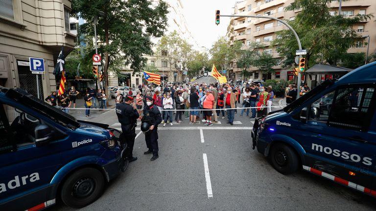 Espagne - des policiers montent la garde alors que les gens manifestent devant le consulat d'Italie, à la suite de l'arrestation de l'ancien chef du gouvernement catalan Carles Puigdemont en Sardaigne jeudi,