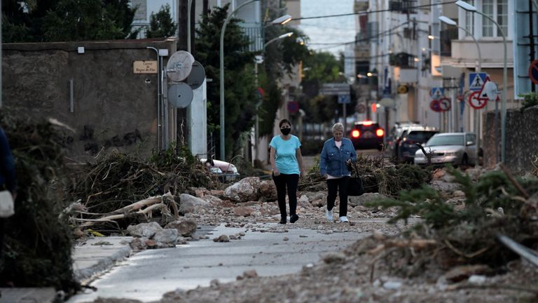 Women walk through a street blocked by fallen trees and rocks after flooding caused by heavy rains in Alcanar, Spain