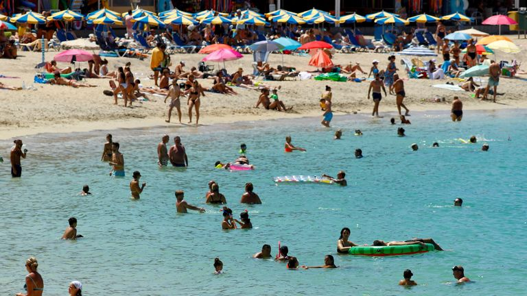 Tourists bathe in the Amadores beach in the south of the island of Gran Canaria, Spain.