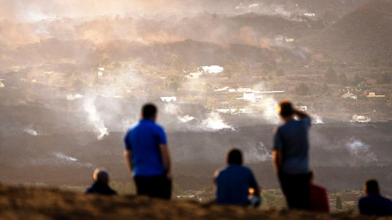 Residents look from a hill as the lava from a volcano eruption flows on the island of La Palma in the Canaries, Spain PIC:AP