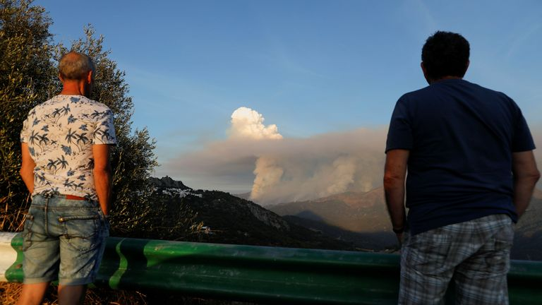 People look on as smoke rises into the sky