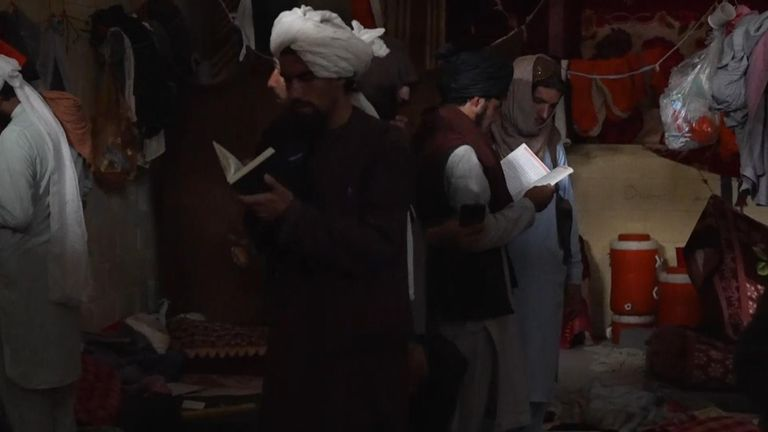 Taliban fighters flip through books and rifle through the belongings