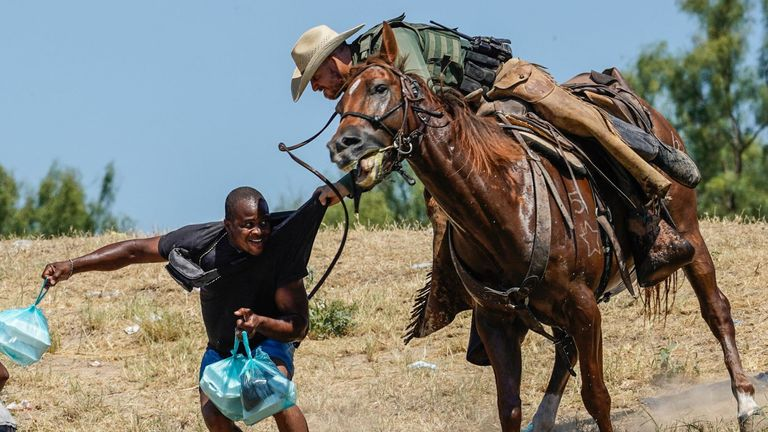 United States Border Patrol agent on horseback tries to stop a Haitian migrant from entering an encampment on the banks of the Rio Grande near the Acuna Del Rio International Bridge in Del Rio, Texas on September 19, 2021. - The United States said Saturday it would ramp up deportation flights for thousands of migrants who flooded into the Texas border city of Del Rio, as authorities scramble to alleviate a burgeoning crisis for President Joe Biden's administration