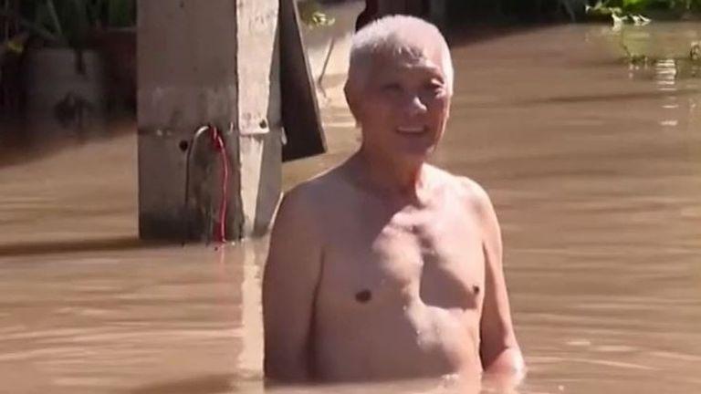 Man stands waist-high in flood waters in northern Thailand