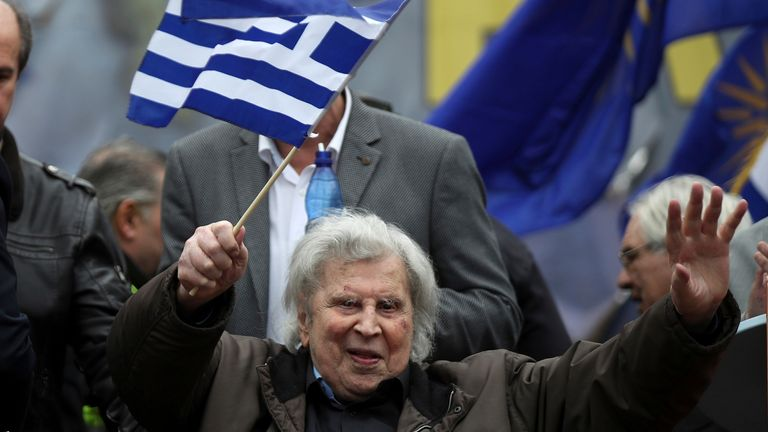 FILE - In this Sunday, Feb. 4, 2018 file photo, famous Greek composer Mikis Theodorakis waves a Greek flag after his speech at a rally in Athens, Greece. Mikis Theodorakis, the beloved Greek composer whose rousing music and life of political defiance won acclaim abroad and inspired millions at home, died on Thursday, Sept. 2, 2021. He was 96. (AP Photo/Petros Giannakouris, File)