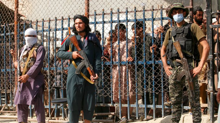 Taliban fighters guard the border alongside a Pakistani paramilitary soldier. Pic: AP