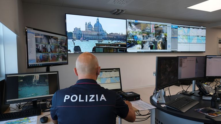 A police officer looks at monitors overseeing the lagoon city, in Venice