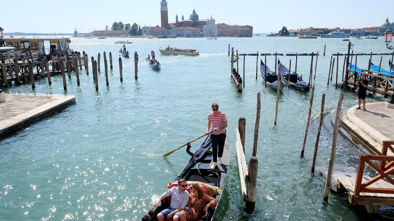 People ride on a gondola as the municipality prepares to charge tourists up to 10 Euro for entry into the lagoon city, in order to cut down the number of visitors, in Venice, Italy, September 5, 2021. Picture taken September 5, 2021. REUTERS/Manuel Silvestri