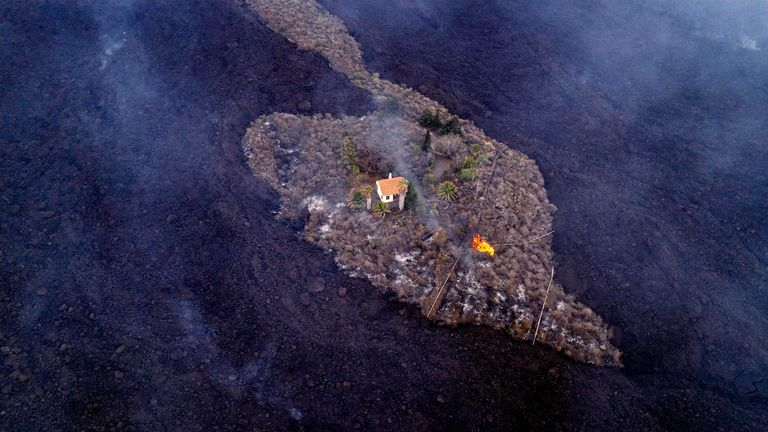 A house remains intact as lava flows after a volcano erupted near Las Manchas on the island of La Palma  PIC:AP